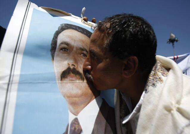 Um apoiante do ex-presidente iemenita Abu Abdullah Saleh beija o seu retrato fotográfico durante uma manifestação em 7 de novembro de 2014 em Sanaa