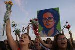 Mulheres carregam flores e retrato de Dilma enquanto militante anti-ditadura em um ato de 19 de abril de 2016 no Planalto