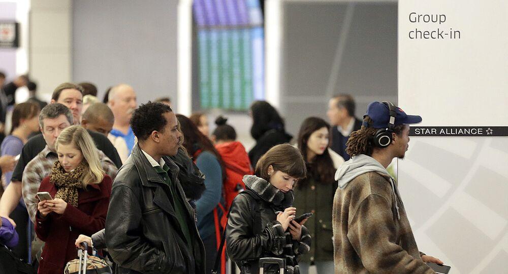 Passageiros esperam em fila da United Airlines