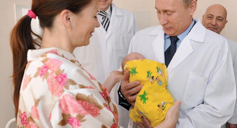 Em 2 de novembro de 2011, Vladimir Putin, então primeiro-ministro da Rússia, segura o bebê de Elena Nikoleyeva, escolhido simbolicamente como o habitante nº 7 bilhões da Terra, nascido dois dias antes no centro perinatal de Kaliningrado.