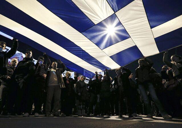 Manifestantes pró-governo erguem bandeira da Grécia.