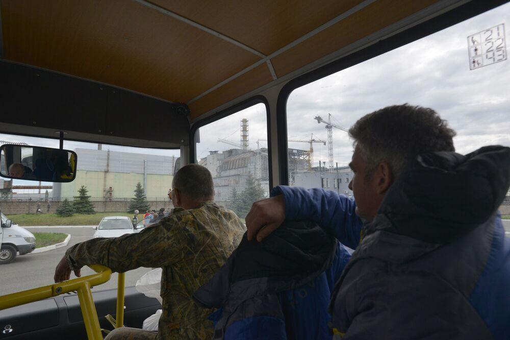 Ônibus passa ao lado de ruínas do quarto bloco do reator da usina nuclear do Chernobyl