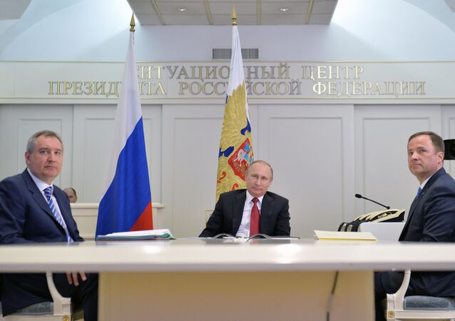 Vladimir Putin, na companhia do vice-premier Dmitry Rogozin (esquerda) e do diretor da Roscosmos, Igor Komarov (direita)