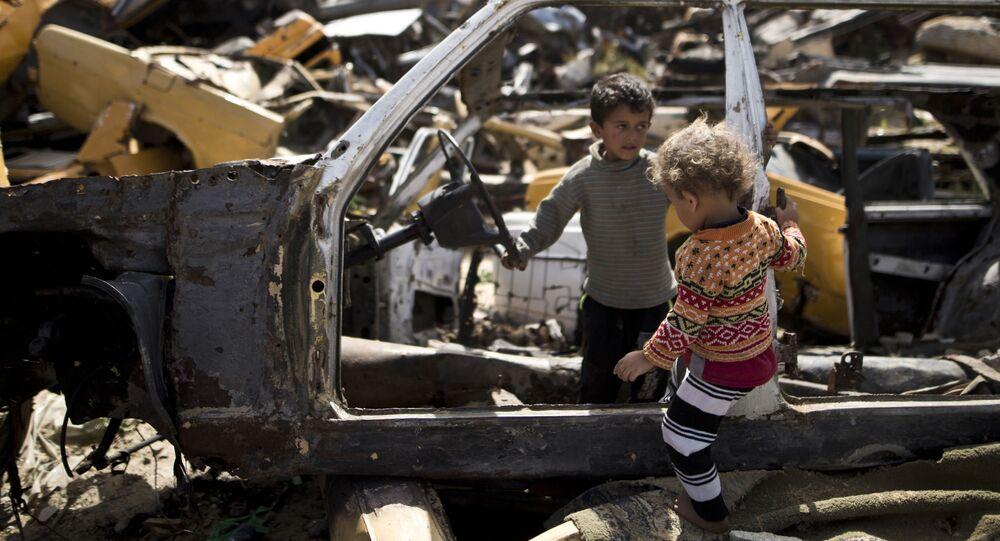Crianças palestinas brincam em um cemitério de carros na região pobre do setor de Gaza