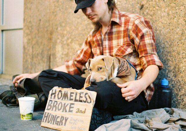 Um sem-teto pedindo o dinheiro na rua