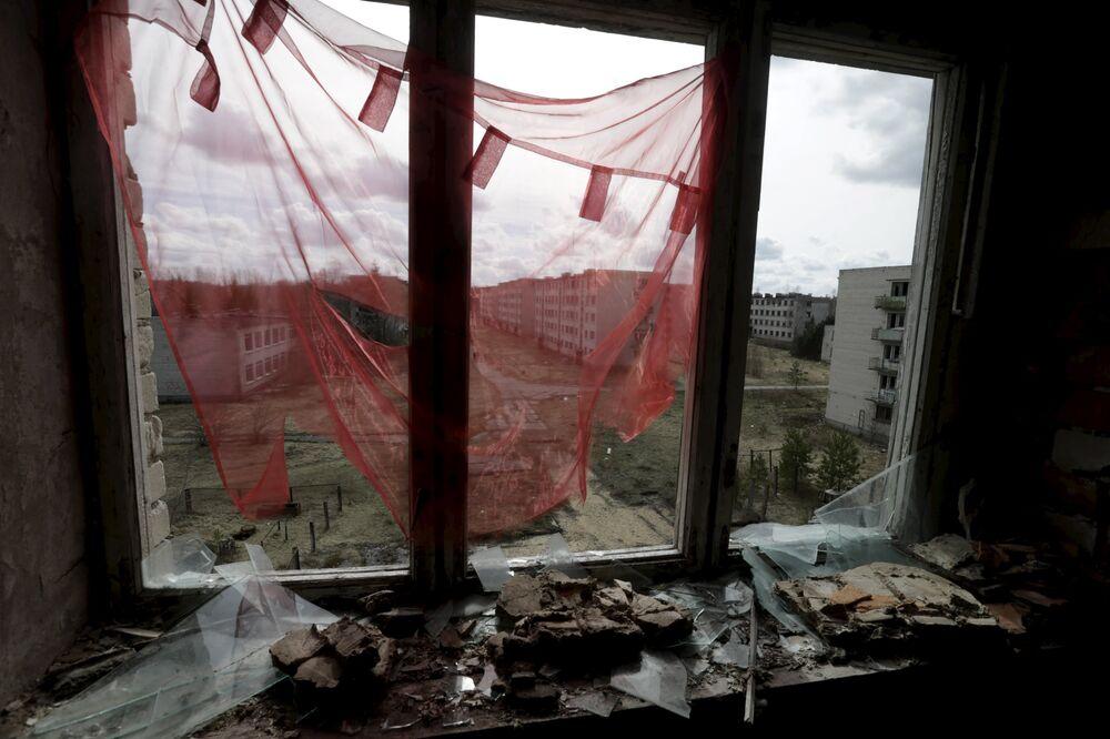 Cortina vermelha perante uma janela quebrada na cidade fantasma de Skrunda-1, Letônia, 9 de abril, 2016