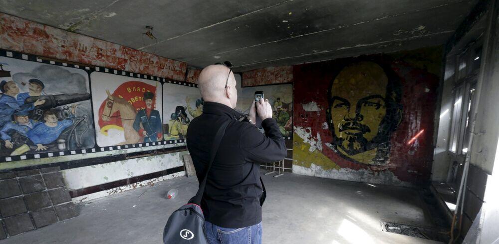 Um homem tira fotos na sala de um ginásio abandonado na cidade fantasma de Skrunda-1, Letônia, 9 de abril, 2016