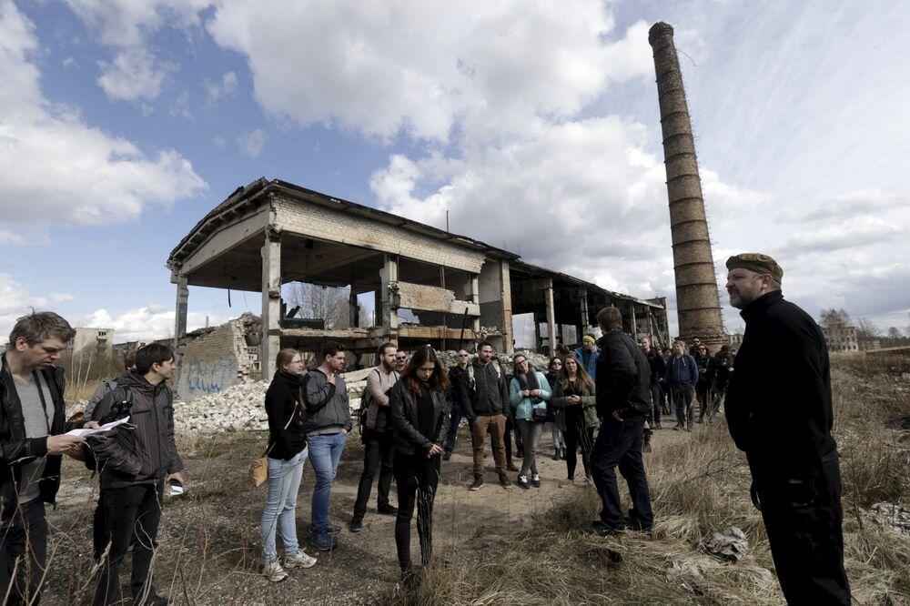 Turistas ouvem um guia (R) durante um passeio turístico na cidade fantasma sede de antiga estação soviética de radares perto da cidade de Skrunda, Letônia, 9 de abril, 2016