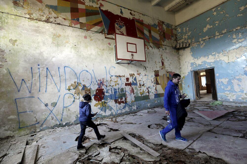 Pessoas andam pelo ginásio na cidade-fantasma da antiga estação soviética de radares perto da cidade de Skrunda, Letônia, 9 de abril, 2016