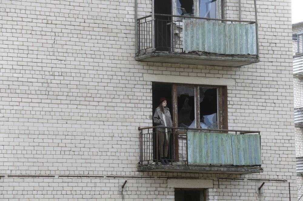 Uma menina olha do balcão do bloco de apartamentos na cidade-fantasma da antiga estação soviética de radares perto da cidade de Skrunda, Letônia, 9 de abril, 2016