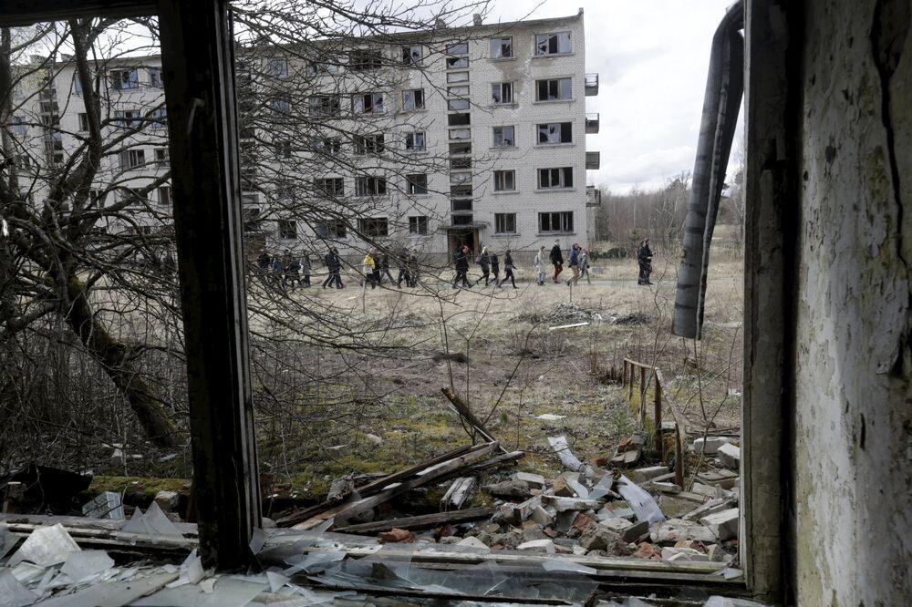 Um grupo de pessoas passam por um prédio abandonado da antiga estação soviética de radares perto da cidade de Skrunda, Letônia, 9 de abril, 2016