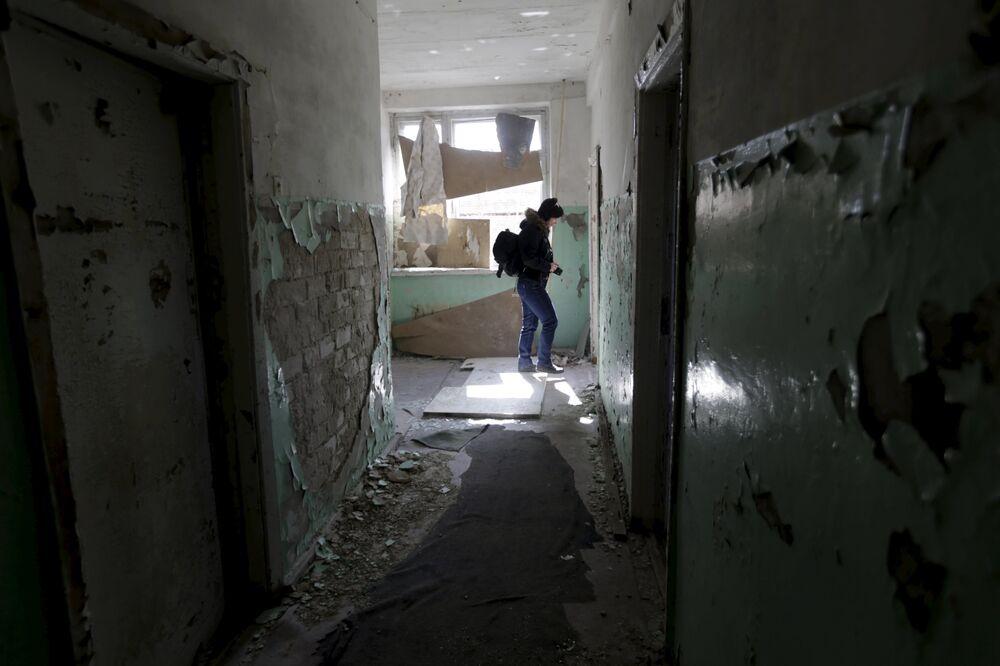 Uma menina anda pelo hospital abandonado na cidade fantasma da antiga estação soviética de radares perto da cidade de Skrunda, Letônia, 9 de abril, 2016