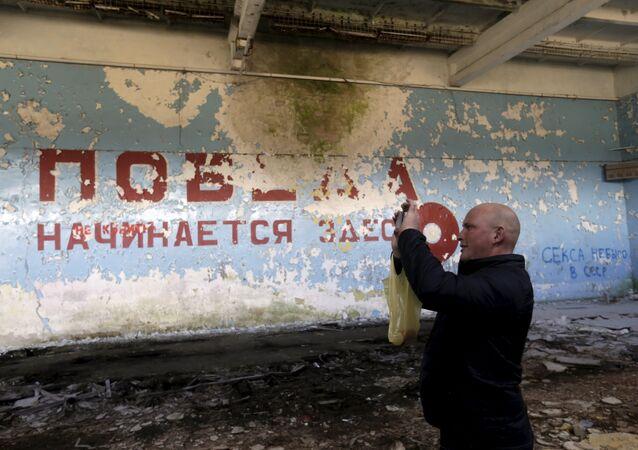 """Um homem tira fotos em pavilhão esportivo perto da cidade de Skrunda, Letônia, 9 de abril, 2016. As palavras em russo pintadas na parede significam """"Vitória começa aqui"""""""
