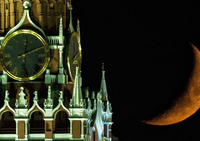 Lua no fundo da Torre Spasskaya de Kremlin de Moscou