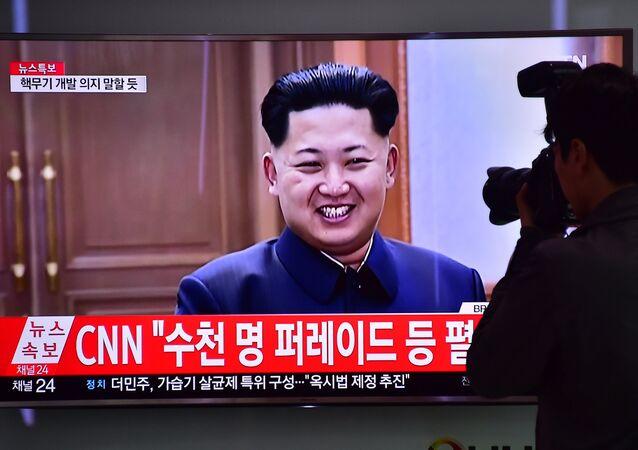 Homem tira uma foto da tela com a imagem do líder norte-coreano Kim Jong-un numa estação ferroviária em Seul, Coreia do Sul, 6 de maio de 2016