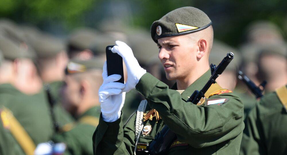 Um soldado fotografa a Parada da Vitória na praça Vermelha em 9 de maio de 2016