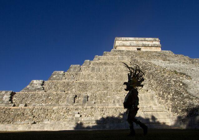 Homem vestindo traje maia passa na frente da pirâmide Kukulcan, no parque arqueológico Chichen Itzá, em 20 de dezembro de 2012.
