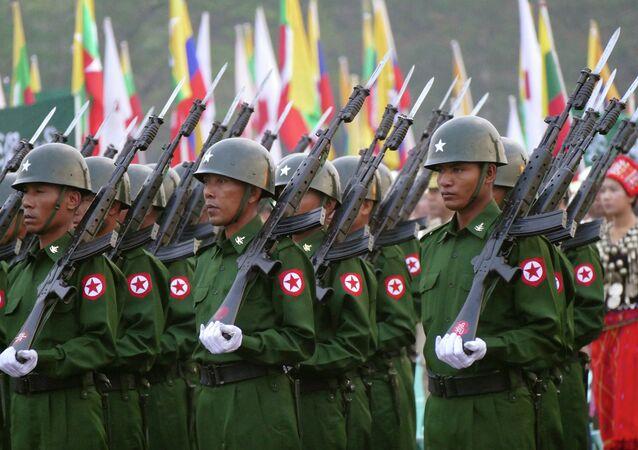 Soldados de Mianmar estão a saudar a bandeira nacional durante uma cerimônia para marcar o 68º aniversário do Dia da União em praça em Yangon, Myanmar, fevereiro 12, 2015.