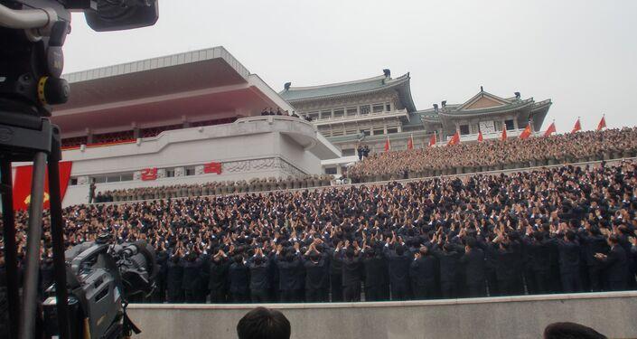 Jornalistas e pessoas presentes no centro de Pyongyang durante o desfile militar de 11 de maio saúdam o líder da Coreia do Norte, Kim Jong-un