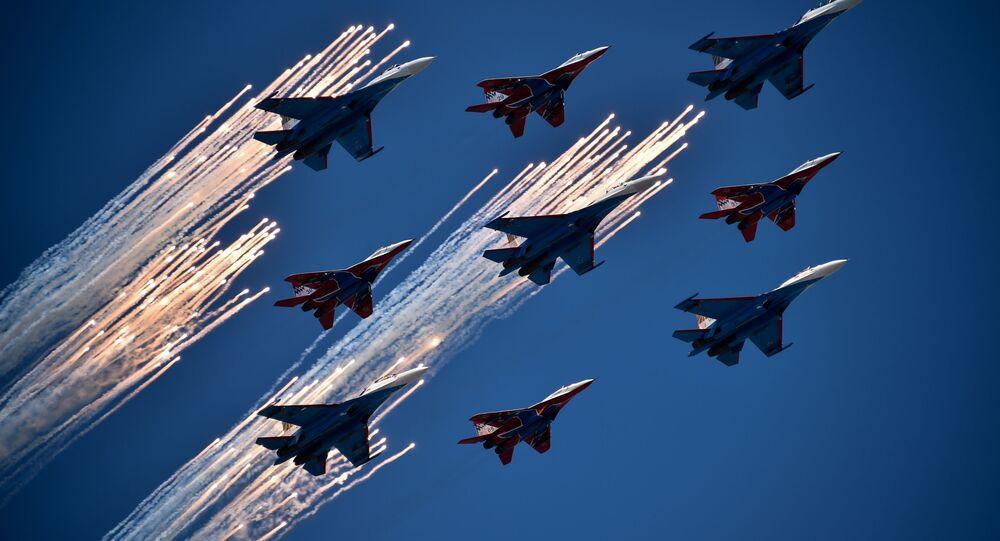 Caças russas Su-27 e MIG-29 voam sobre a Praça vermelha durante a Parada Militar em comemoração a Dia da Vitória em Moscou