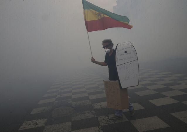 Ativista frances de máscara de gas com bandeira antiga de Etiópia na mão tenta impedir violência entre policiais e manifistantes