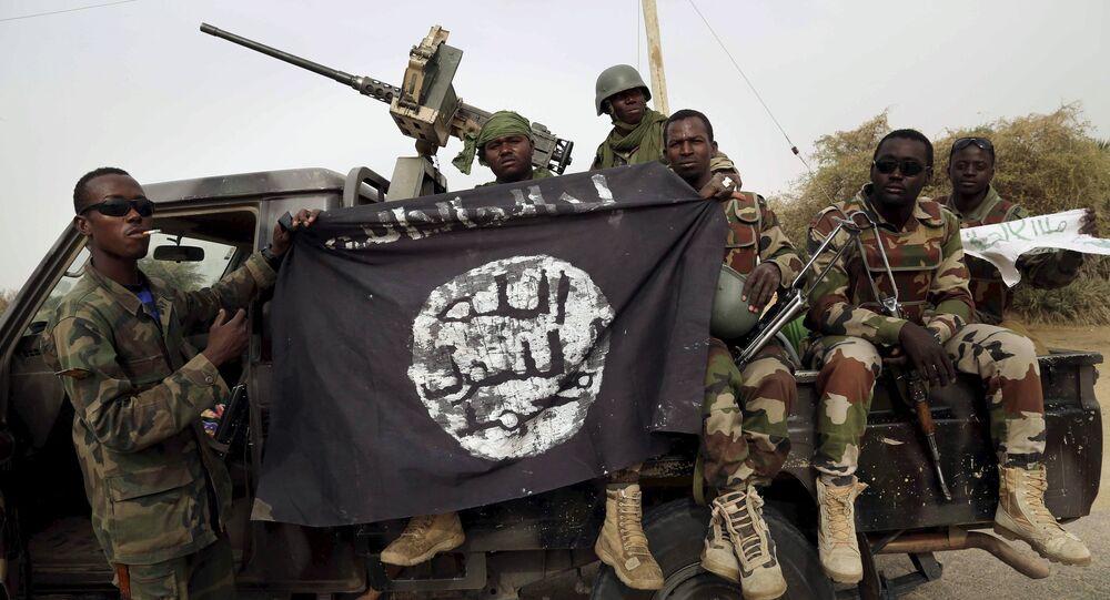 Soldados nigerianos exibem bandeira do Boko Haram apreendida na retomada da cidade de Damasak, em 18 de março de 2015