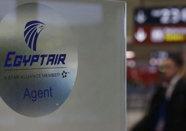 Homem passa ao lado do logotipo da companhia aérea EgyptAir no aeroporto Charles de Gaulle, Paris, França