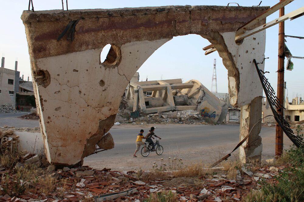 Meninos sírios em bicicleta, na cidade síria de Daraa