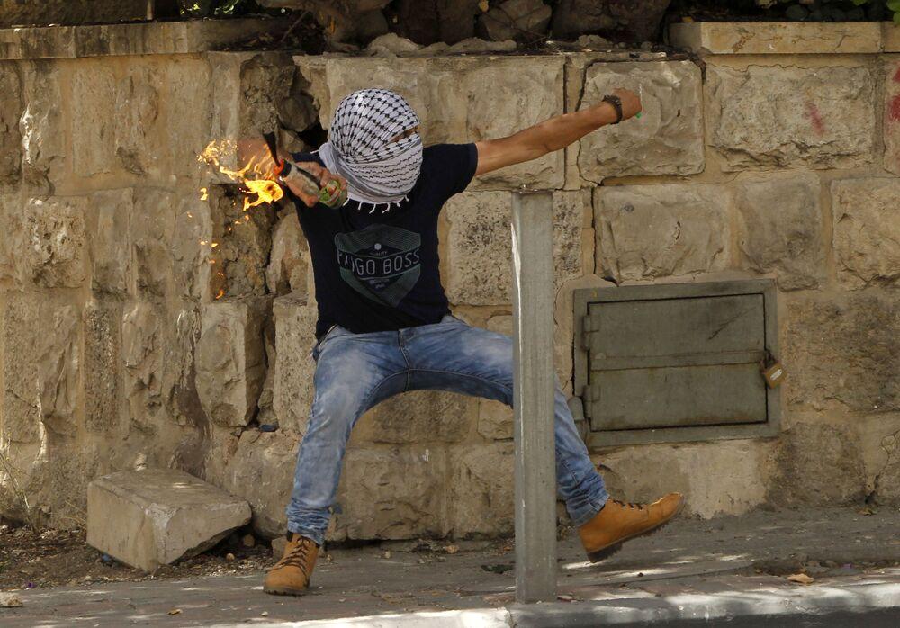 Um palestino atira uma bomba incendiário contra as forças de segurança israelenses durante confrontos