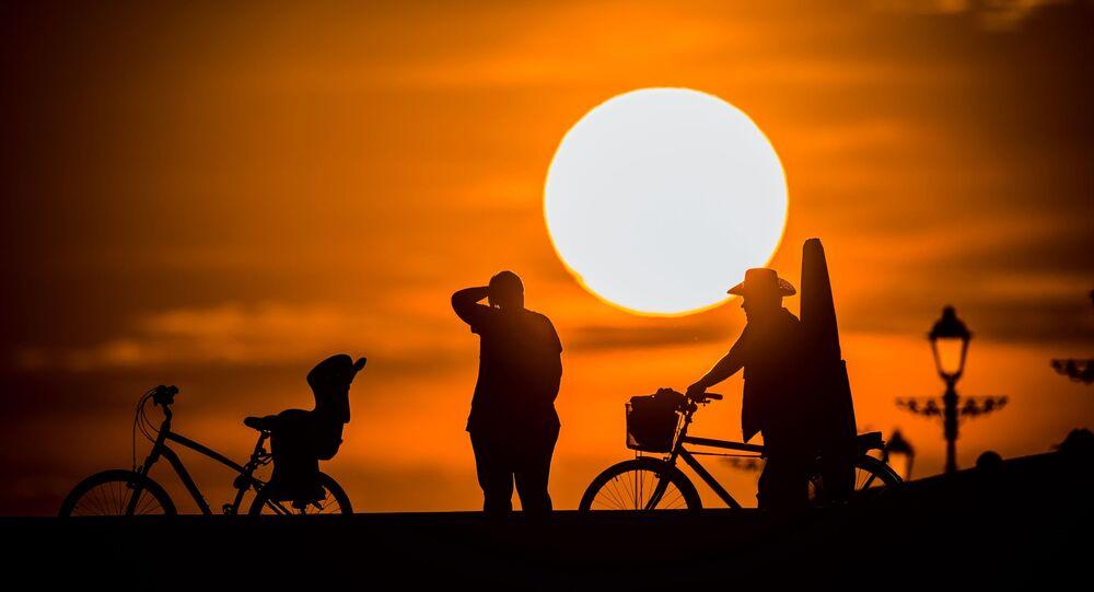 Ciclistas no pôr-do-sol à beira-mar perto do Parque Olímpico em Sochi (Rússia)