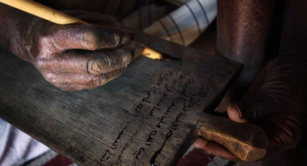 Escrituras corânicos de carvão, cola e água sobre uma placa de madeira
