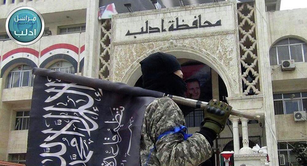 Militante da Frente al-Nusra com a bandeira do grupo na província de Idlib, Síria