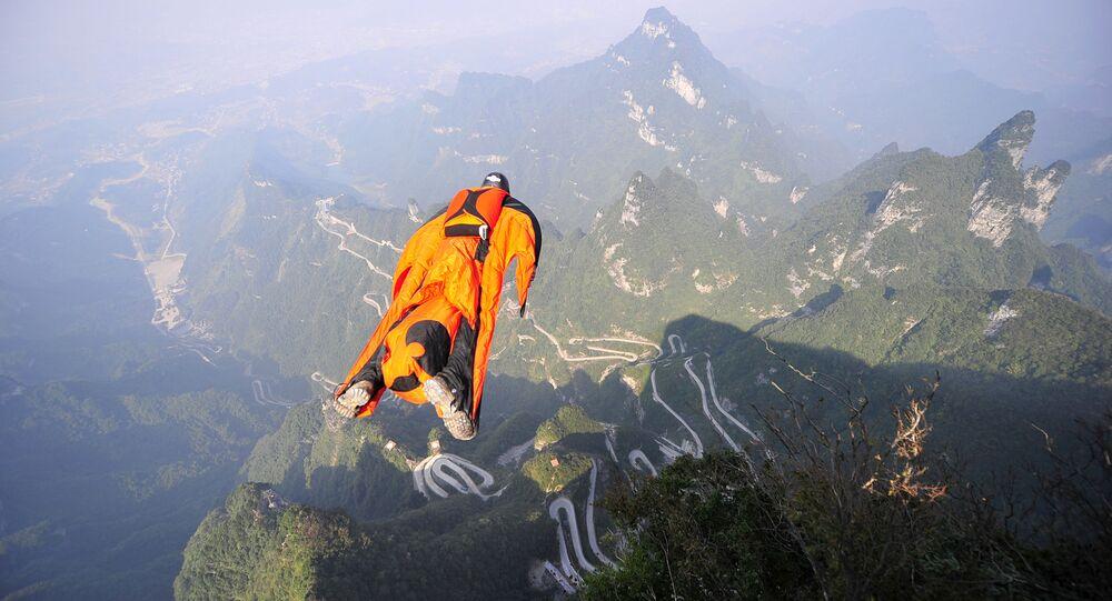 Húngaro Victor Kovats de traje planador salta na vale em Zhangjiajie, província de Hunan da China.