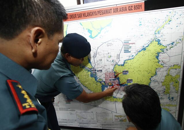 Navy soldiers work on a map of Indonesia monitoring all Navy ships from Indonesia, Singapore, and Malaysia involved in the joint search and rescue operation for AirAsia flight QZ8501 at a navy base on Batam island, December 29, 2014