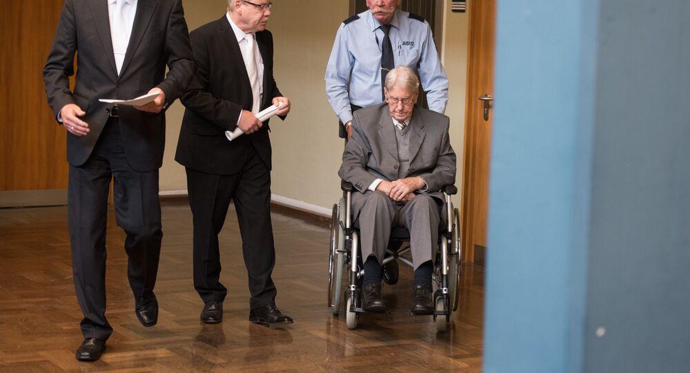 Reinhold Hanning chega ao tribunal na Alemanha em sua cadeira de rodas, acompanhado pelos advogados