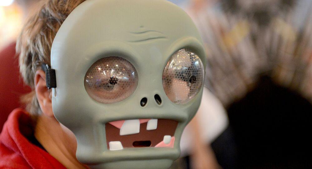 Visitante da exibição IgroMir (Mundo de jogos) vestindo um máscara de zumbi do jogo Plant vs. Zombies, Moscou, Rússia (foto de arquivo)