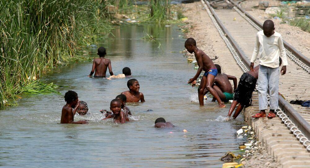 Crianças brincando em um reseratório de água ao lado de uma ferrovia em Luanda, Angola