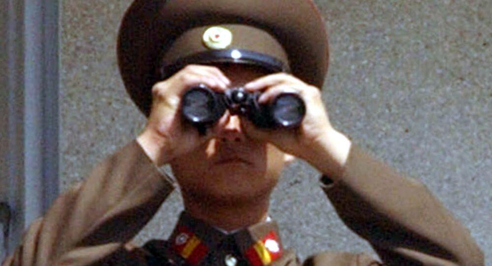 Um militar norte-coreano usa um binóculo