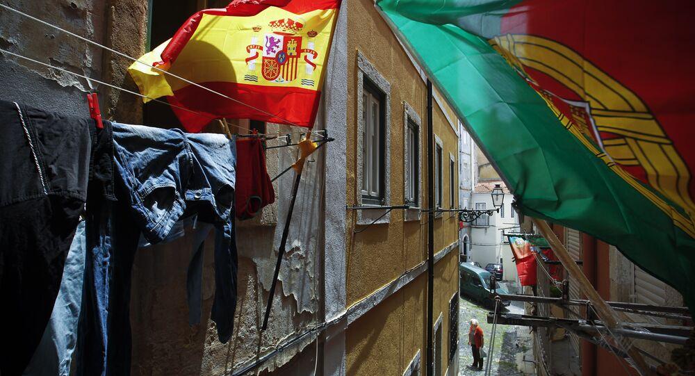 Bandeiras de Portugal e Espanha em balcões numa rua estreita em Lisboa