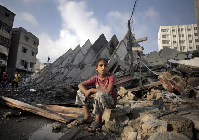 Menino palestiniano sentado sobre ruínas depois de bombardeio da Faixa de Gaza por Israel