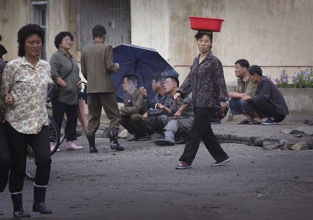 Uma mulher norte-coreana equilibra um balde na cabeça, enquanto homens fumam na rua no final de um dia de trabalho, na quarta-feira, 22 de junho de 2016, em Wonsan, Coreia do Norte.