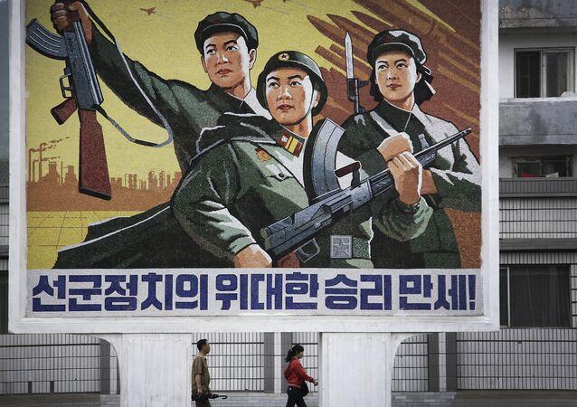 """Um homem e uma mulher norte-coreanos caminham sob um mural com uma mensagem que diz: """"Viva a grande vitória da política 'Exército em primeiro lugar'!"""" no centro da cidade de Wonsan, na quarta-feira, 22 de junho de 2016, em Wonsan, Coreia do Norte."""