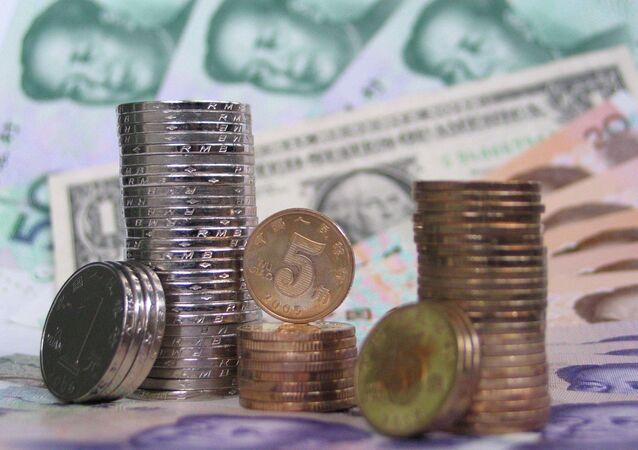 Moedas e notas de yuan chinês em torno de um dólar norte-americano