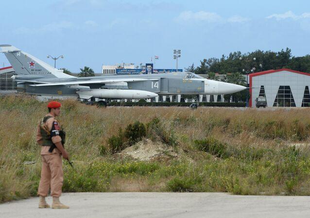 Um militar russo e o avião Su-24 na pista da base aérea de Hmeymim, Síria