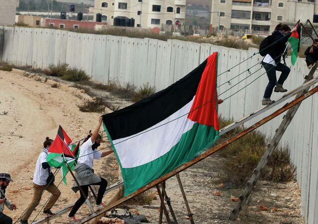 Ativistas estrangeiros e palestinos usam rampa para atravessar barreira israelense