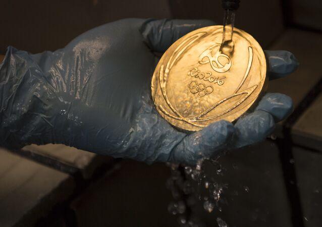 Um trabalhador limpa uma medalha de ouro dos Jogos Olímpicos no Rio 2016 após seu banho de ouro em uma fábrica de moeda no Rio de Janeiro