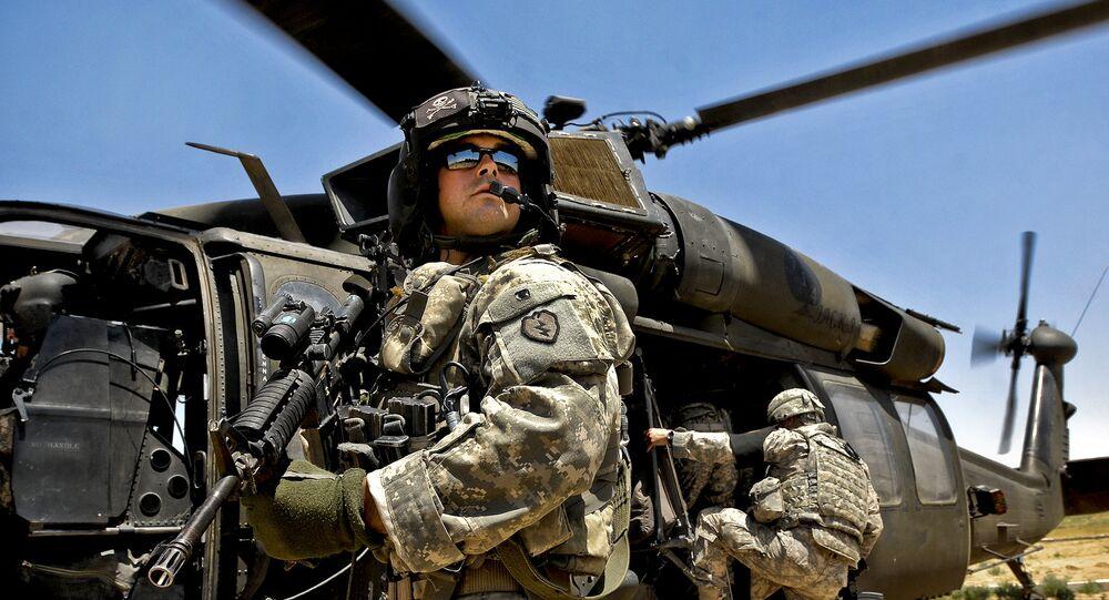 O soldado estadunidense em frente do helicóptero UH-60 Black Hawk em Iraque