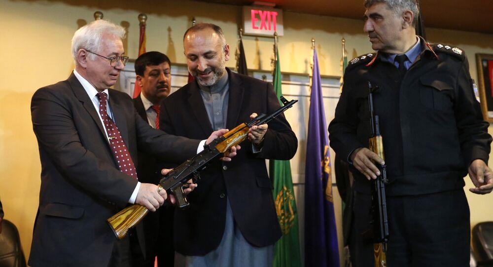 Embaixador da Rússia no Afeganistão, Alexander Mantytskiy, demonstra um AK-47 ao Mohammad Hanif Atmar, Conselheiro de Segurança Nacional do Afeganistão