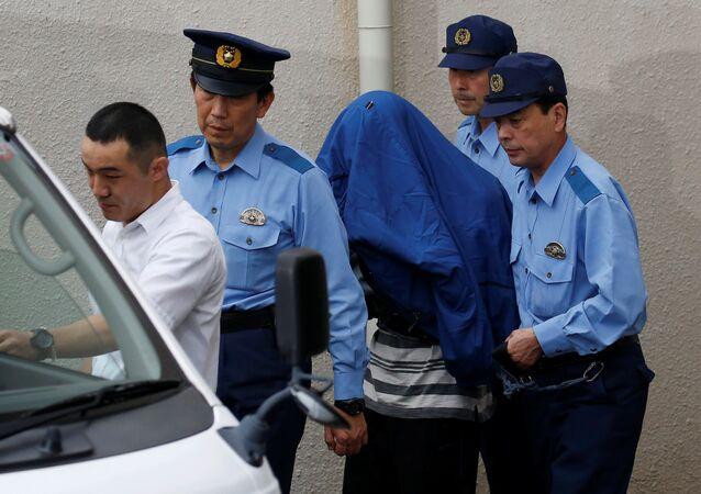 Satoshi Uematsu, suspeito de um ataque mortal em um centro para deficientes, é escoltado por policiais quando ele é levado ao Ministério Público.Sagamihara, Japão. Julho, 27, 2016