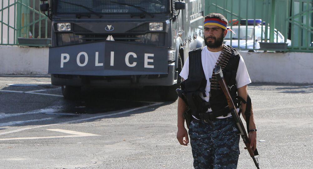 Um homem armado caminha para dentro da delegacia Erebuni tomada pelos membros do movimento de oposição em Yerevan. Julho 23, 2016.